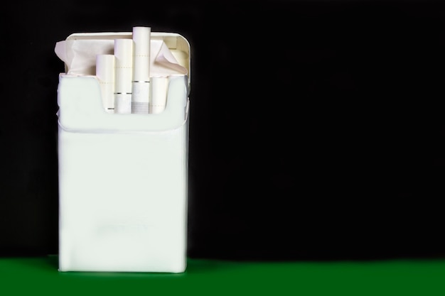 A pack of cigarettes on a dark background beside a green background