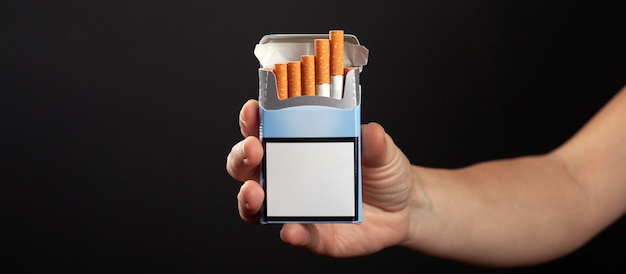 Pack of cigarettes in hand on dark