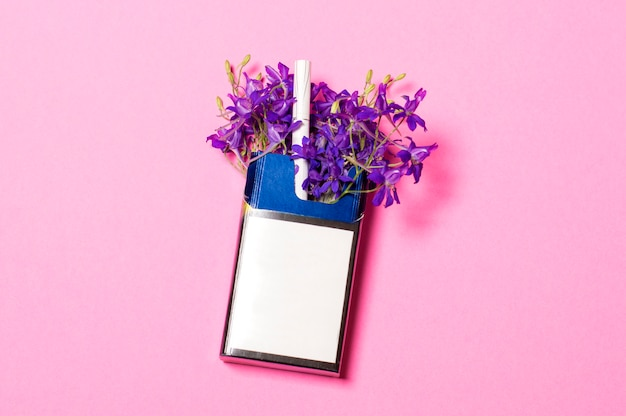 A pack of cigarettes on a pink background in a pack of blue flowers