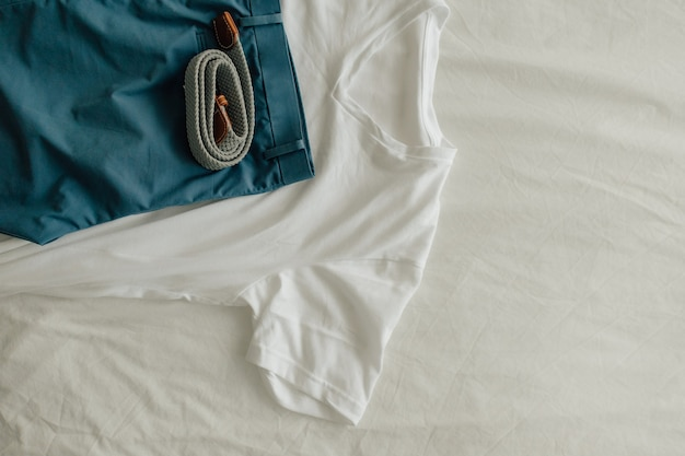 Pack of clothes on white bed with a white t-shirt blue short and clothe belt.