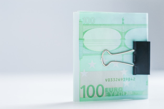 Pack of euro notes lies on a white table fastened with a paperclip. the concept of savings during the crisis
