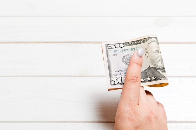 A pack of fifty dollar bills in female hand on wooden background