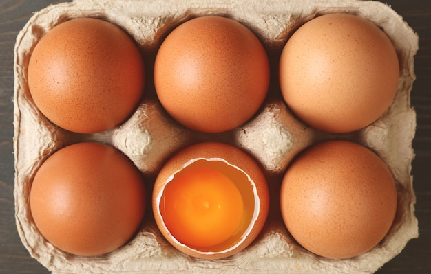Pack of fresh organic eggs with an opened shell one in the carton box
