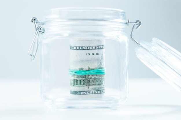 Pack of hundred-dollar bills lies in a glass jar. the concept of savings during the crisis. mixed media