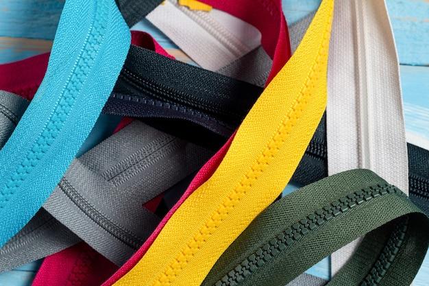 슬라이더가있는 다채로운 플라스틱 및 금속 지퍼 줄무늬를 많이 포장하십시오.