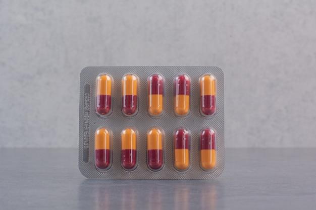 Пакет таблеток антибиотика на мраморном столе.
