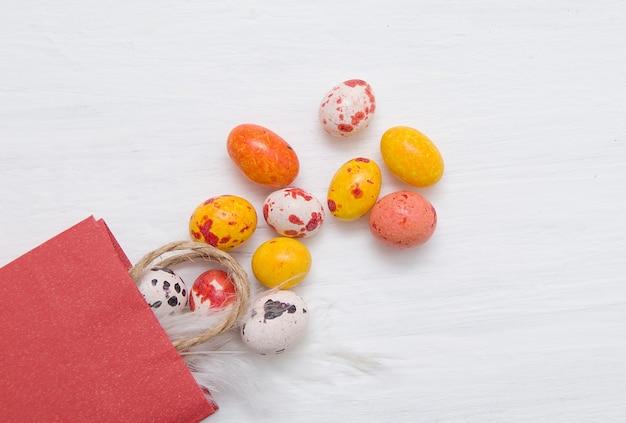 그려진 흰색 나무 배경에 서로 다른 색상의 초콜릿 부활절 달걀 팩