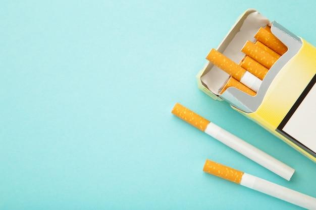 青い背景の上のタバコのパック。喫煙禁止。