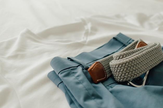 Пакет одежды на белой кровати с белой короткой синей футболкой и поясом одежды.