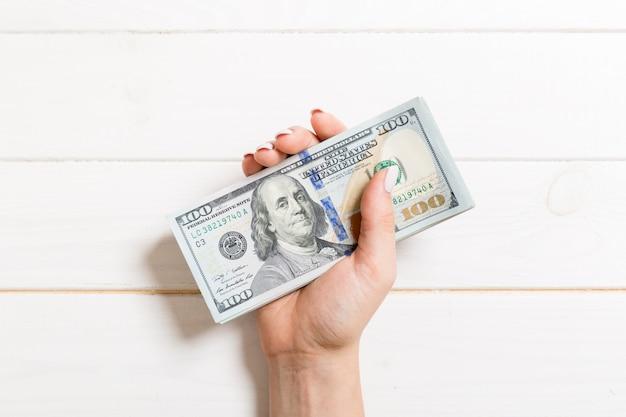 女性の手で100ドル札のパック。お金を節約の概念のトップビュー