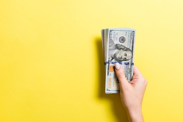 복사 공간이 있는 여성의 손에 100달러 지폐 팩. 화려한 배경에서 돈 절약 개념의 상위 뷰.