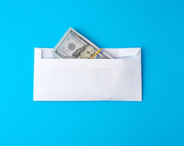 Пачка бумажных американских стодолларовых купюр, перевязанных резинкой и лежащих в белом конверте