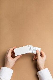 Пачка таблеток в мужских руках макет
