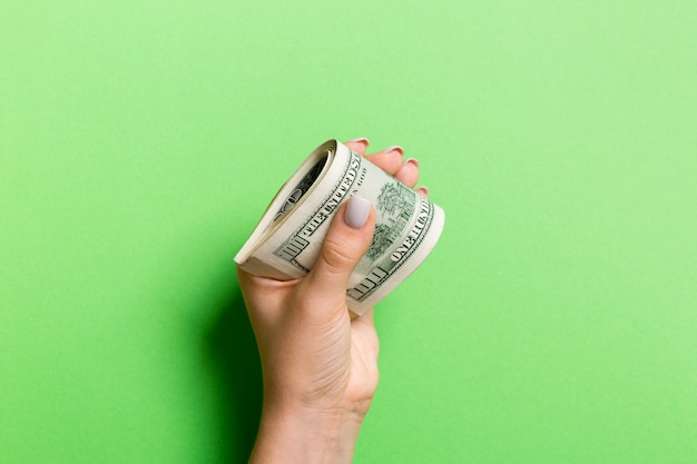 A pack of one hundred dollar bills in female hand on colorful background. salary concept