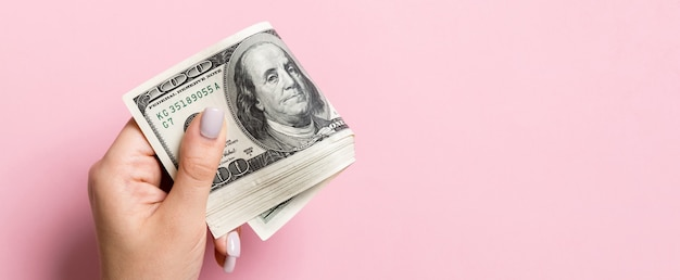 A pack of one hundred dollar bills in female hand on colorful surface. copy space.