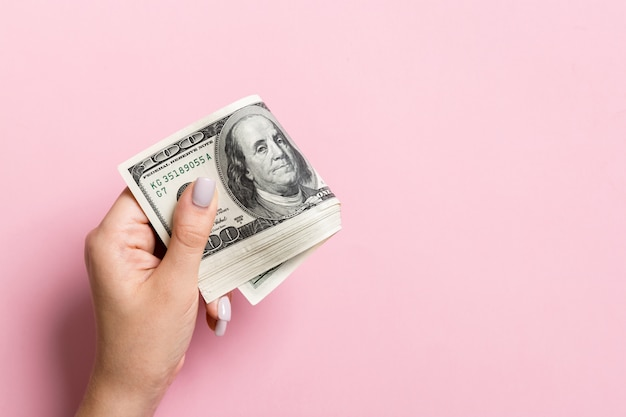 A pack of one hundred dollar bills in female hand. salary concept with copy space