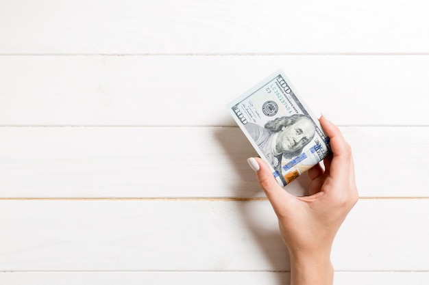 A pack of one hundred dollar bills in female hand on wooden. salary concept with copy space