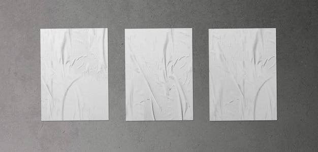 Pack of three crumpled posters on concrete surface