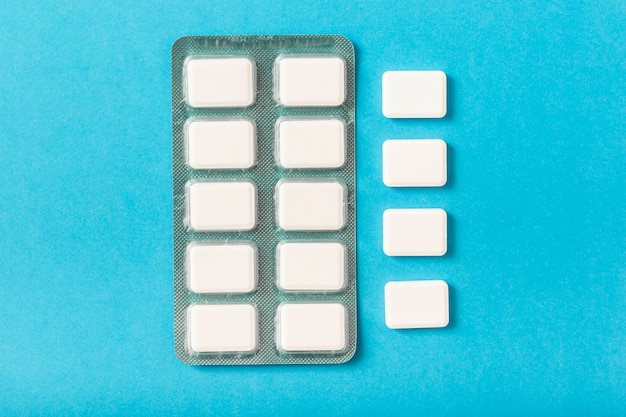 Pack of white chewing gum blister on blue background