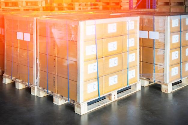 パッケージボックスは、保管倉庫のパレットにプラスチックフィルムを包みました貨物輸送倉庫