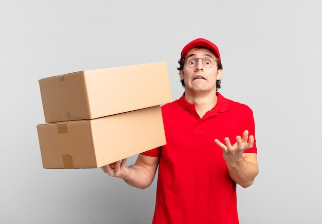 Package deliver boy looking desperate and frustrated, stressed, unhappy and annoyed, shouting and screaming