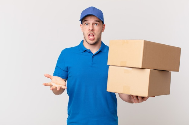 Человек, доставивший посылку, чувствует себя чрезвычайно шокированным и удивленным, встревоженным и паническим, с напряженным и испуганным взглядом.