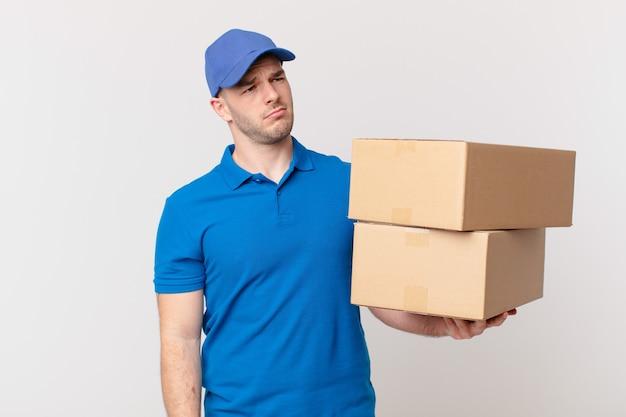 パッケージは、悲しみ、動揺、または怒りを感じ、否定的な態度で横を向いて、意見の相違に眉をひそめている男性を届けます