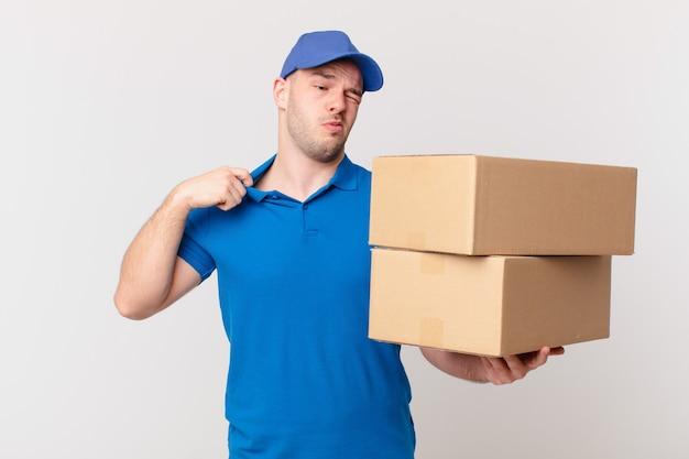 Посылка доставляет мужчине, который чувствует стресс, тревогу, усталость и разочарование, дергает за шею рубашки, выглядит разочарованным из-за проблемы