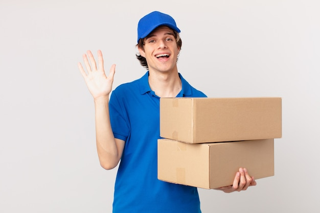Package deliver man smiling happily, waving hand, welcoming and greeting you