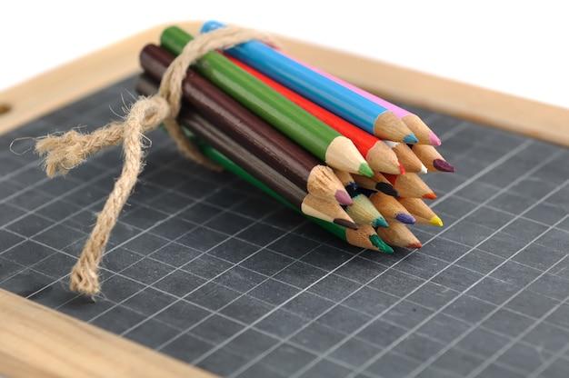 白い背景の上のスレートに色鉛筆のパッケージ