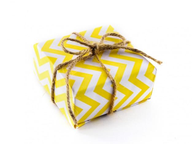 Упакованный подарок в желтой бумаге на белой поверхности