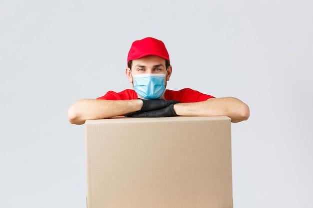 패키지 및 소포 배달, covid-19 검역 및 이전 주문. 빨간 유니폼 모자, 안면 마스크, 장갑을 낀 젊은 택배, 배달하기 위해 상자에 기대어 주문 배송, 회색 배경