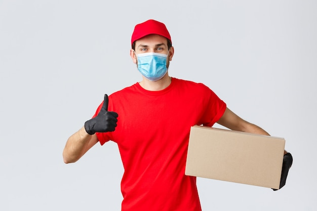 Packages and parcels delivery, covid-19 quarantine delivery, transfer orders. cheerful courier in red uniform, gloves and face mask, thumb-up, recommend contactless deliver, holding box with order