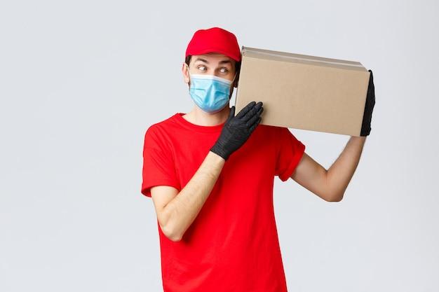 Consegna di pacchi e pacchi, consegna in quarantena covid-19, ordini di trasferimento. corriere curioso in uniforme rossa, guanti e maschera protettiva, consegna la scatola al cliente, porta l'ordine senza contatto