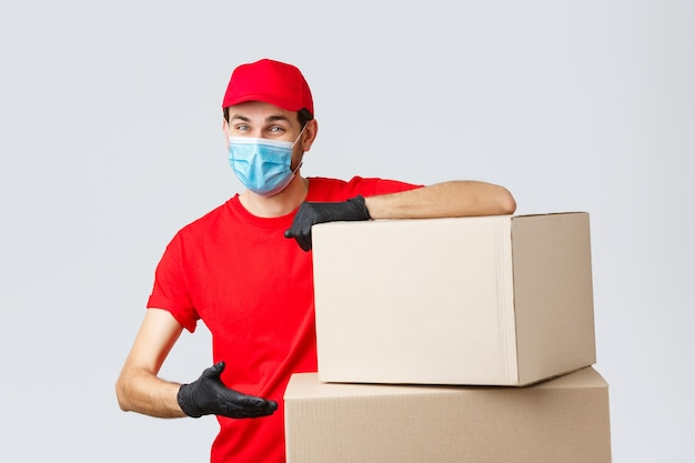 Packages and parcels delivery, covid-19 quarantine and transfer orders. smiling courier in red uniform, gloves and medical face mask, introduce boxes to transfer your order, recommend service