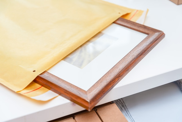 紙のバブル封筒にアートの額縁をパッケージ化