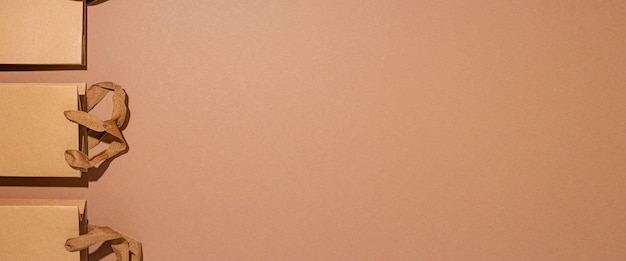ギフト用のパッケージバッグ、茶色の段ボールの背景に茶色のクラフト。上面図、フラットレイ。バナー。