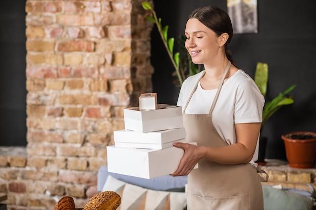 包装、ベーカリー製品。居心地の良い部屋でパン屋の梱包箱を運ぶかなりきちんとした楽しい女性