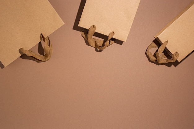 Упаковка подарочная крафт-коричневая упаковка на коричневом картонном фоне. вид сверху, плоская планировка.