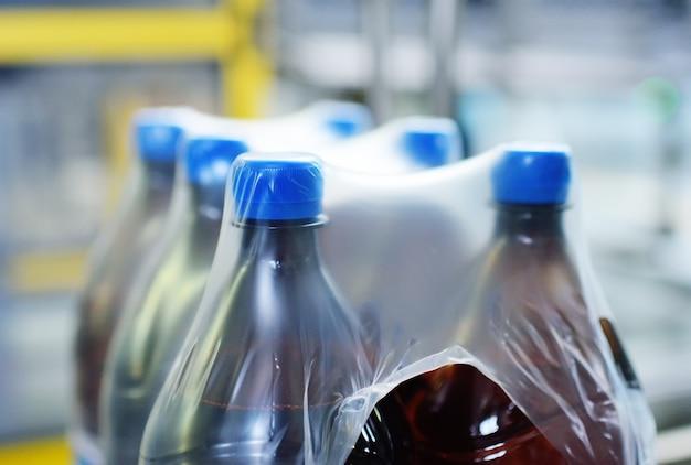 プラスチック製のpetボトルをビールまたは液体でポリエチレンテトラパックに包装。飲料の工業生産。