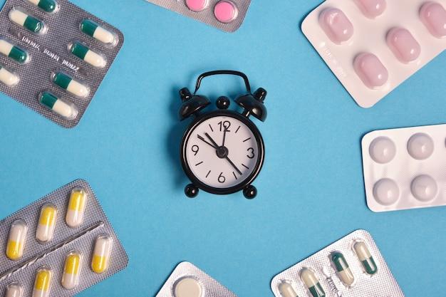 중간에 검은 색 알람 시계가있는 테이블에 정제 및 알약 포장. 파란색 배경, 복사 공간, 약물 시간 초과, 약물 섭취 알림 개념