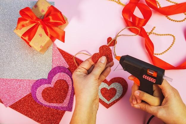 발렌타인 데이 또는 생일 선물 포장. 분홍색 표면에 빨간 종이 마음으로 발렌타인 선물. 평면도. 여성의 손에 종이에서 발렌타인 하트를 만듭니다.