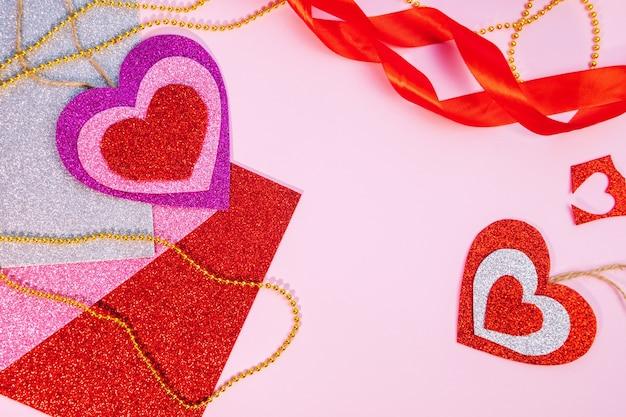 발렌타인 데이 또는 생일 선물 포장. 분홍색 표면에 빨간 종이 마음으로 발렌타인 선물. 평면도. 분홍색 배경. 텍스트를위한 공간.