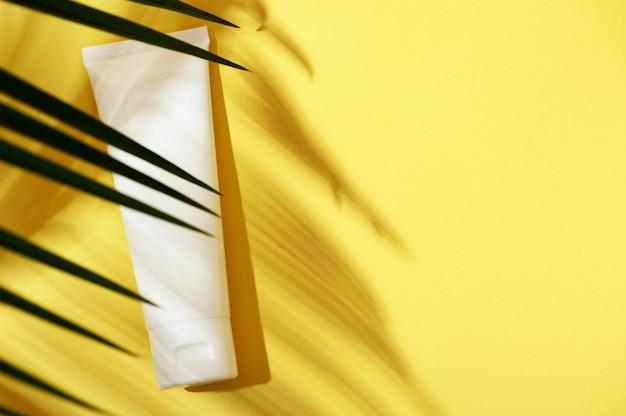 야자수의 그림자가 있는 노란색 밝은 배경에 핸드 크림, 얼굴, 몸, 치약 위쪽 보기를 위한 흰색 플라스틱 튜브를 포장합니다. 여름 뷰티 스킨 케어 개념입니다. 평평한 위치, 복사 공간.