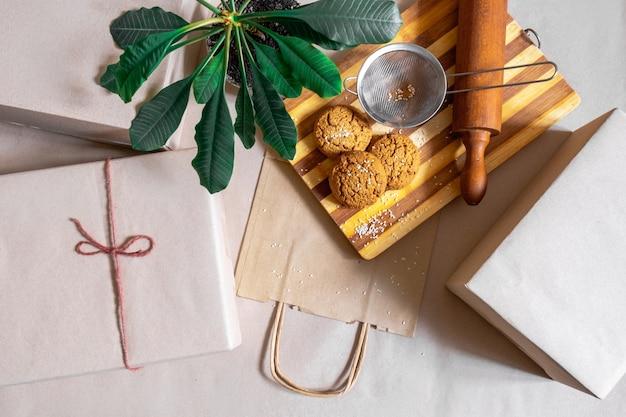 Упакованные коробки, хозяйственная сумка для доставки еды и зеленое растение на сером фоне, вид сверху.