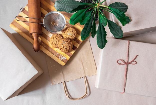 Упакованные коробки, хозяйственная сумка для доставки еды и зеленое растение на сером столе, вид сверху.
