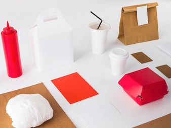 Packed food with disposal cup and sauce bottle on white background