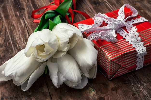 Packed gift box amid a bouquet of white tulips