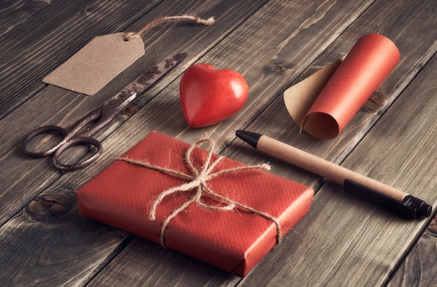 Packed gift box, cord and decorative heart on wooden table