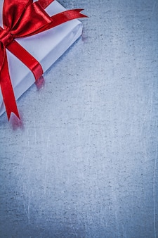 Packed gift with red bow on metallic table